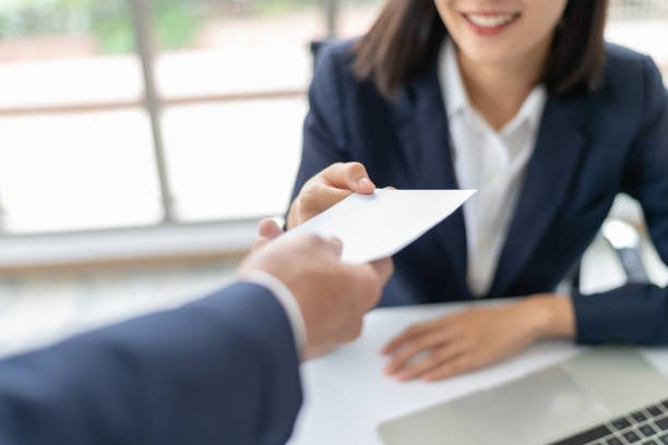Staff receiving salary or bonus money from boss or manager at office happily.